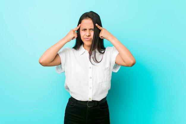 Młoda latynoska chłodna kobieta przy niebieskiej ścianie skupiła się na zadaniu, trzymając palce wskazujące głową.