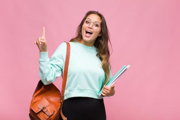 Młoda latynoska czująca się jak szczęśliwa i podekscytowana geniusz po zrealizowaniu pomysłu, radośnie podnosząca palec, eureka!