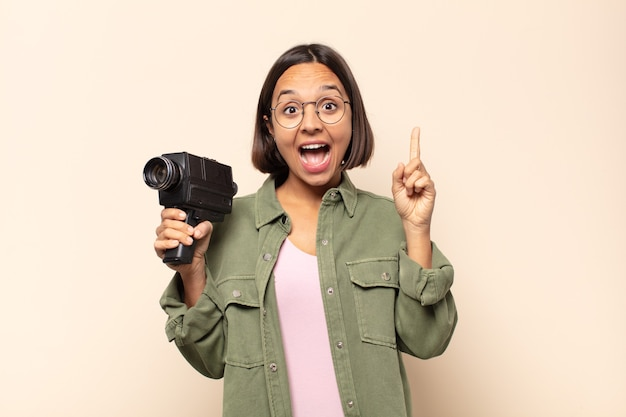 Młoda latynoska czująca się jak szczęśliwa i podekscytowana geniusz po zrealizowaniu pomysłu, radośnie unosząca palec, eureka!