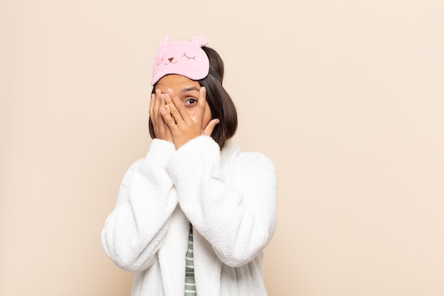Młoda latynoska czuje się przestraszona lub zawstydzona, zerka lub podgląda z oczami na wpół zakrytymi rękami