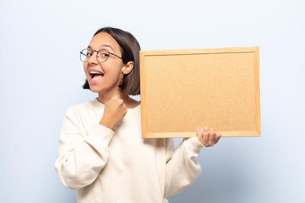 Młoda latynoska czuje się szczęśliwa, pozytywna i odnosząca sukcesy, zmotywowana, gdy mierzy się z wyzwaniem lub świętuje dobre wyniki