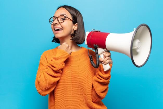 Młoda latynoska czuje się szczęśliwa, pozytywna i odnosząca sukcesy, zmotywowana, gdy staje przed wyzwaniem lub świętuje dobre wyniki