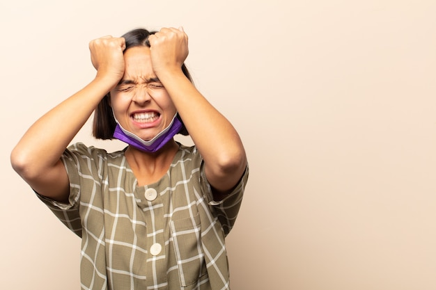 Młoda latynoska czuje się zestresowana i niespokojna, przygnębiona i sfrustrowana bólem głowy, podnosząc obie ręce do głowy