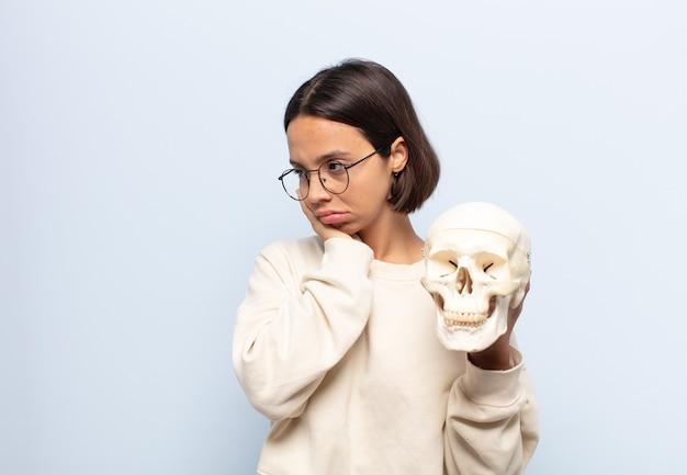 Młoda latynoska czuje się znudzona, sfrustrowana i senna po męczącym, nudnym i żmudnym zadaniu, trzymając twarz ręką