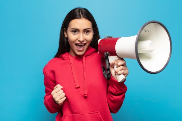 Młoda latynoska czuje się zszokowana, podekscytowana i szczęśliwa, śmiejąca się i świętująca sukces, mówiąc wow!