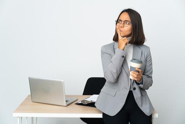 Młoda latynoska kobieta biznesu pracująca w biurze na białym tle, mająca wątpliwości podczas patrzenia w górę