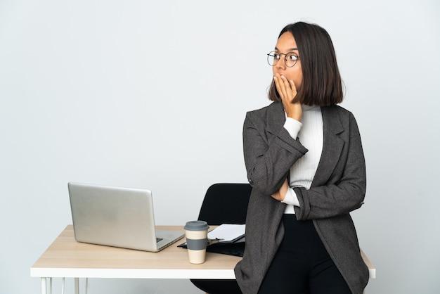 Młoda latynoska kobieta biznesu pracująca w biurze na białym tle robi gest zaskoczenia, patrząc w bok