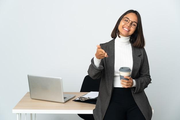 Młoda latynoska kobieta biznesu pracująca w biurze na białym tle, ściskając ręce, aby zamknąć dobrą ofertę