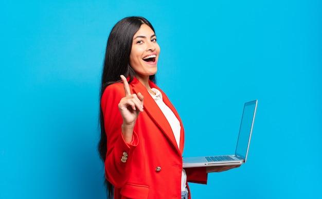 Młoda latynoska kobieta czując się jak szczęśliwy i podekscytowany geniusz po zrealizowaniu pomysłu, radośnie podnosząc palec, eureka!. koncepcja laptopa