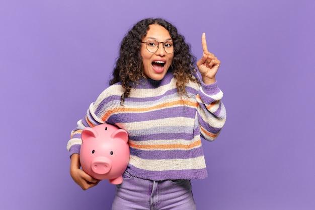 Młoda latynoska kobieta czując się jak szczęśliwy i podekscytowany geniusz po zrealizowaniu pomysłu, radośnie podnosząc palec, eureka!. koncepcja skarbonki