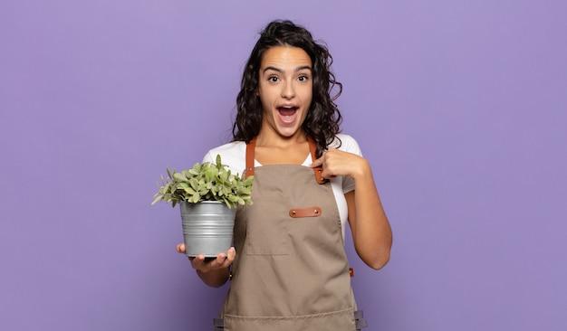 Młoda latynoska kobieta czująca się szczęśliwa, zdziwiona i dumna, wskazująca na siebie z podekscytowanym, zdumionym spojrzeniem