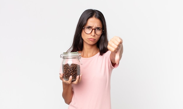 Młoda latynoska kobieta czuje krzyż, pokazując kciuk w dół i trzymając butelkę ziaren kawy