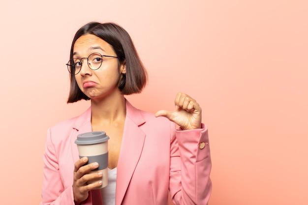 Młoda latynoska kobieta czuje się dumna, arogancka i pewna siebie, wygląda na zadowoloną i odnoszącą sukcesy, wskazując na siebie