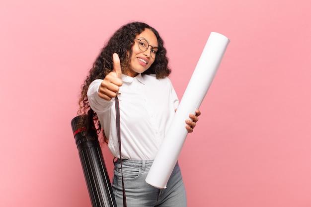 Młoda latynoska kobieta czuje się dumna, beztroska, pewna siebie i szczęśliwa, uśmiechając się pozytywnie z kciukami do góry. koncepcja architekta