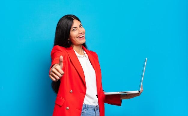 Młoda latynoska kobieta czuje się dumna, beztroska, pewna siebie i szczęśliwa, uśmiechając się pozytywnie z kciukami do góry. koncepcja laptopa