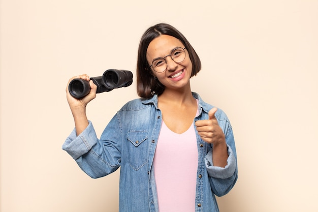 Młoda latynoska kobieta czuje się dumna, beztroska, pewna siebie i szczęśliwa, uśmiechając się pozytywnie z kciukami w górę