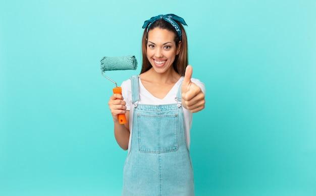 Młoda latynoska kobieta czuje się dumna, uśmiecha się pozytywnie z kciukami do góry i maluje ścianę