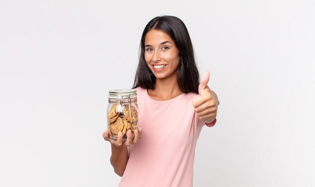 Młoda latynoska kobieta czuje się dumna, uśmiecha się pozytywnie z kciukami do góry i trzyma szklaną butelkę po ciastkach