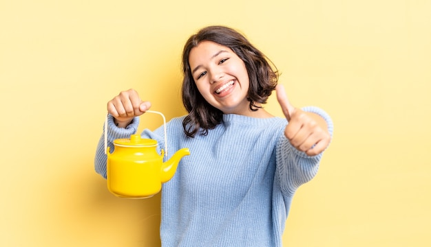 Młoda latynoska kobieta czuje się dumna, uśmiechając się pozytywnie z kciukami do góry. koncepcja czajnika