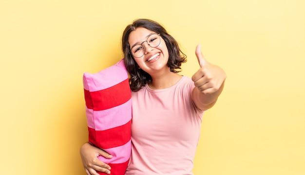 Młoda latynoska kobieta czuje się dumna, uśmiechając się pozytywnie z kciukami do góry. koncepcja porannego przebudzenia