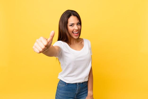 Młoda latynoska kobieta czuje się dumna, uśmiechając się pozytywnie z kciukami w górę