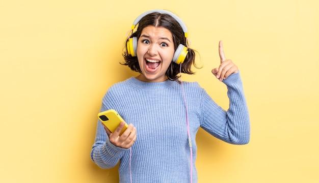Młoda latynoska kobieta czuje się jak szczęśliwy i podekscytowany geniusz po zrealizowaniu pomysłu. koncepcja słuchawek i smartfona