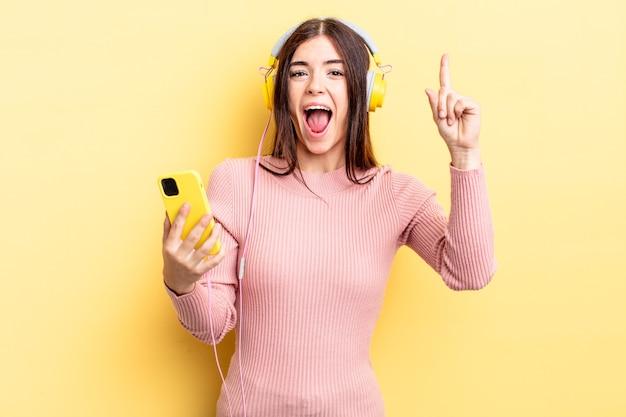 Młoda latynoska kobieta czuje się jak szczęśliwy i podekscytowany geniusz po zrealizowaniu pomysłu. koncepcja słuchawek i telefonu