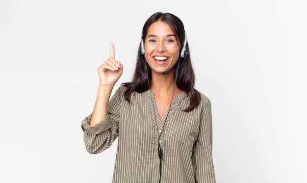 Młoda latynoska kobieta czuje się jak szczęśliwy i podekscytowany geniusz po zrealizowaniu pomysłu z zestawem słuchawkowym. koncepcja telemarketingu