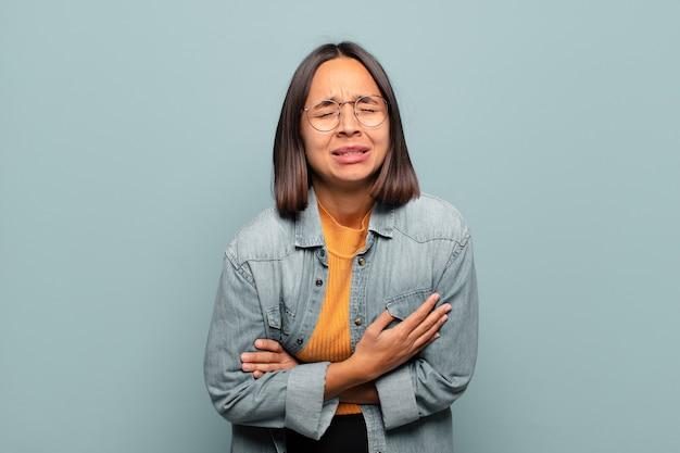Młoda latynoska kobieta czuje się niespokojna, chora, chora i nieszczęśliwa, cierpi na bolesny ból brzucha lub grypę