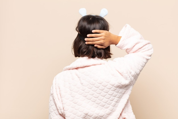 Młoda latynoska kobieta czuje się niezorientowana i zdezorientowana, myśląc o rozwiązaniu, z ręką na biodrze, a drugą na głowie, widok z tyłu