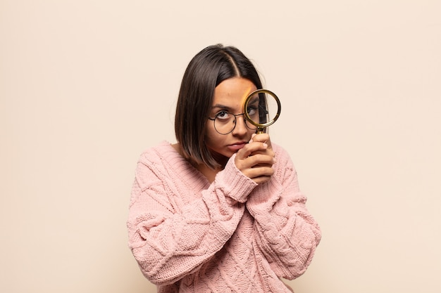 Młoda latynoska kobieta czuje się przestraszona lub zawstydzona, zerka lub szpieguje z oczami na wpół zakrytymi rękami