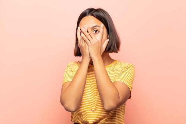 Młoda latynoska kobieta czuje się przestraszona lub zawstydzona, zerkająca lub szpiegująca z oczami do połowy zakrytymi rękami