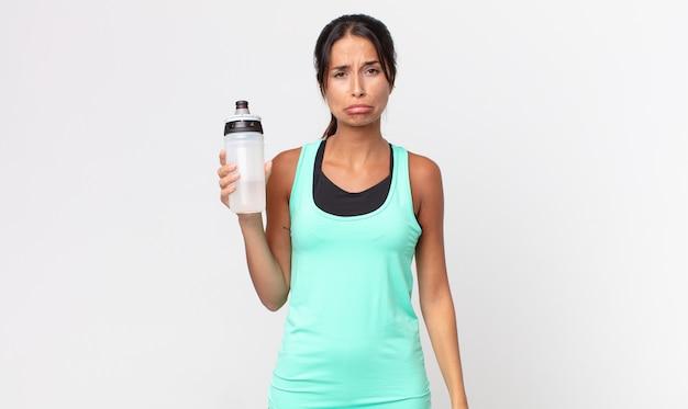 Młoda latynoska kobieta czuje się smutna i jęczy z nieszczęśliwym spojrzeniem, płacze i trzyma butelkę wody. koncepcja fitness