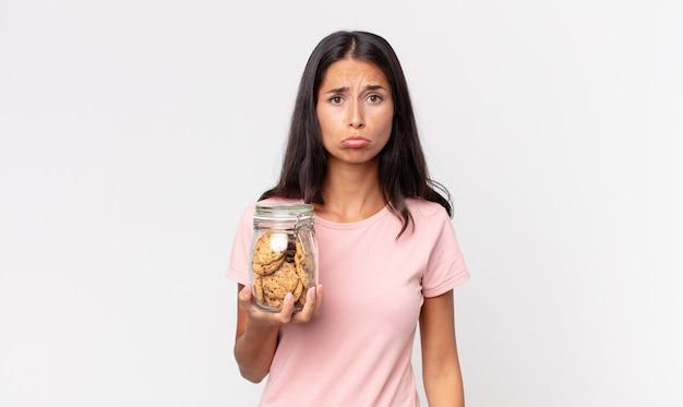 Młoda latynoska kobieta czuje się smutna i jęczy z nieszczęśliwym spojrzeniem, płacze i trzyma szklaną butelkę po ciastkach