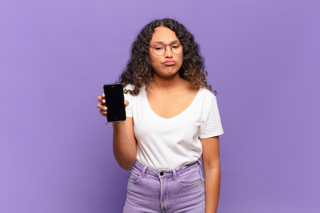 Młoda latynoska kobieta czuje się smutna i marudna z nieszczęśliwym spojrzeniem, płacze z negatywnym i sfrustrowanym nastawieniem. koncepcja inteligentnego telefonu
