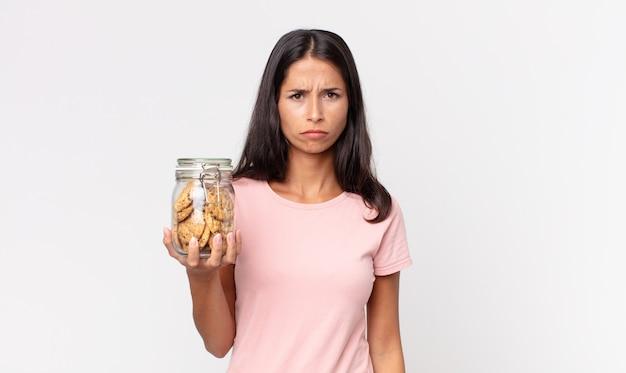 Młoda latynoska kobieta czuje się smutna, zdenerwowana lub zła i patrzy w bok i trzyma szklaną butelkę po ciastkach