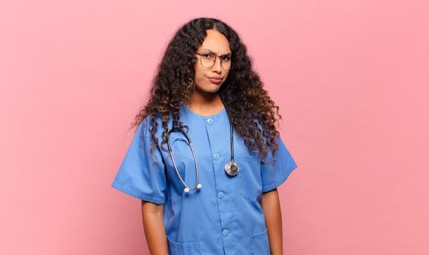 Młoda latynoska kobieta czuje się smutna, zdenerwowana lub zła i patrzy w bok z negatywnym nastawieniem, marszcząc brwi w niezgodzie. koncepcja pielęgniarki