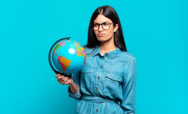 Młoda latynoska kobieta czuje się smutna, zdenerwowana lub zła i patrzy w bok z negatywnym nastawieniem, marszcząc brwi w niezgodzie. koncepcja planety ziemi