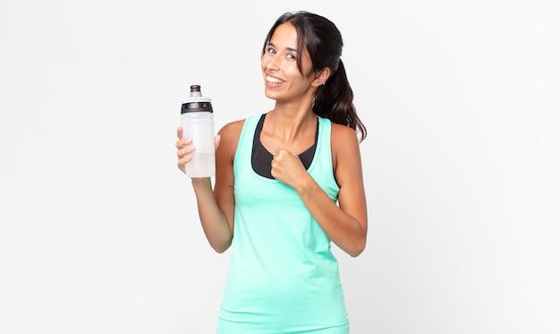Młoda latynoska kobieta czuje się szczęśliwa i staje przed wyzwaniem lub świętuje i trzyma butelkę wody. koncepcja fitness