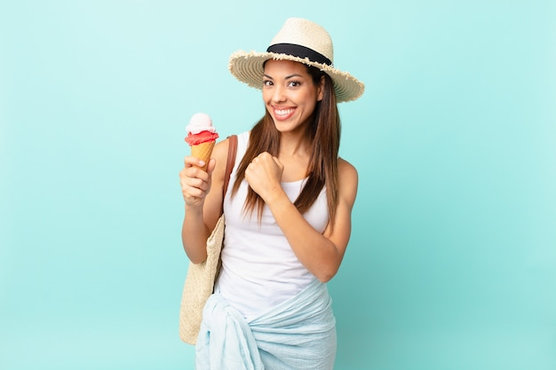 Młoda latynoska kobieta czuje się szczęśliwa i staje przed wyzwaniem lub świętuje i trzyma lody. koncepcja suma