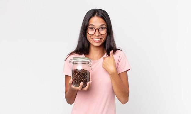 Młoda latynoska kobieta czuje się szczęśliwa i wskazuje na siebie z podekscytowaną i trzymającą butelkę ziaren kawy