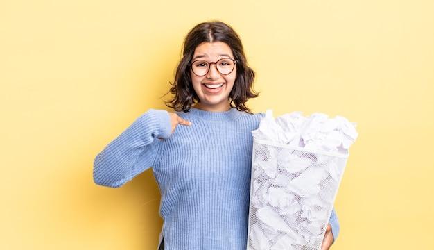 Młoda latynoska kobieta czuje się szczęśliwa i wskazuje na siebie z podekscytowaną koncepcją porażki na śmieci