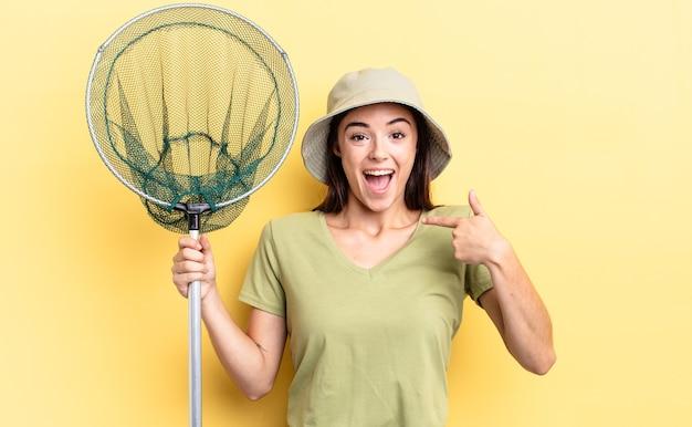 Młoda latynoska kobieta czuje się szczęśliwa i wskazuje na siebie z podekscytowaną koncepcją sieci rybnej