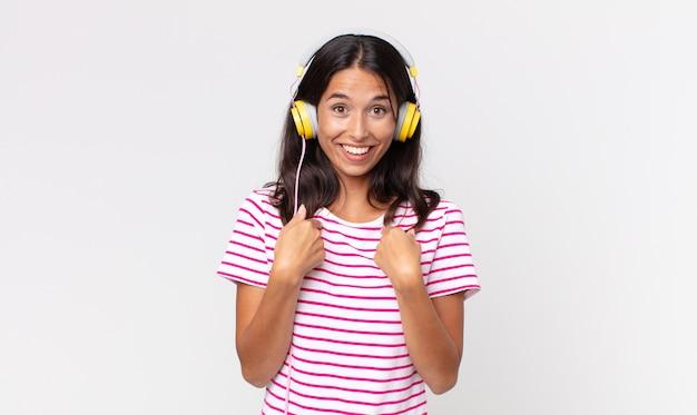 Młoda latynoska kobieta czuje się szczęśliwa i wskazuje na siebie z podekscytowaną muzyką w słuchawkach