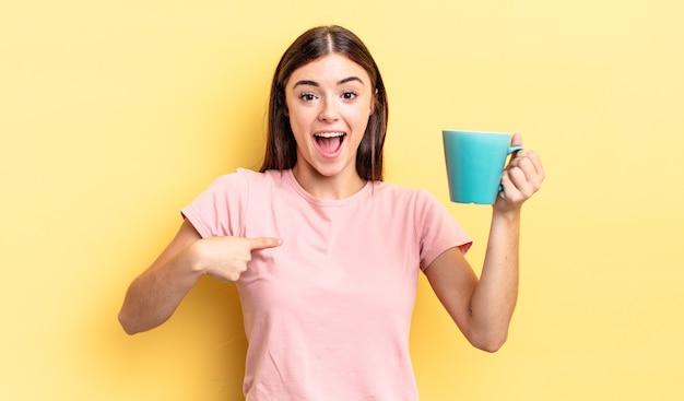 Młoda latynoska kobieta czuje się szczęśliwa i wskazuje na siebie z podekscytowaniem. koncepcja filiżanki kawy