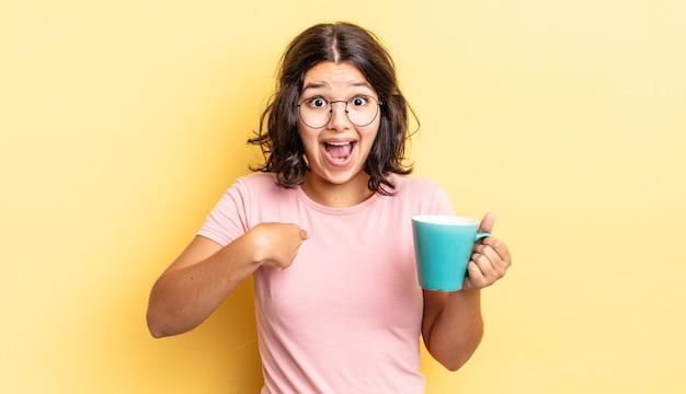 Młoda latynoska kobieta czuje się szczęśliwa i wskazuje na siebie z podekscytowaniem. koncepcja kubek kawy