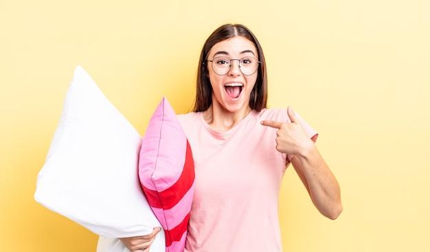 Młoda latynoska kobieta czuje się szczęśliwa i wskazuje na siebie z podekscytowaniem. koncepcja piżamy i poduszki