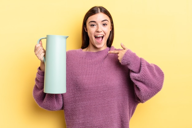 Młoda latynoska kobieta czuje się szczęśliwa i wskazuje na siebie z podekscytowaniem. koncepcja termosu do kawy