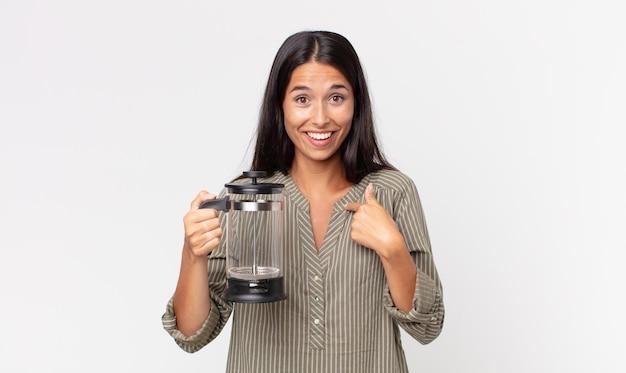 Młoda latynoska kobieta czuje się szczęśliwa i wskazuje na siebie z podekscytowanym i trzymającym ręczny ekspres do kawy