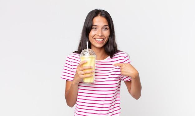 Młoda latynoska kobieta czuje się szczęśliwa i wskazuje na siebie z podekscytowanym i trzymającym waniliowy koktajl mleczny